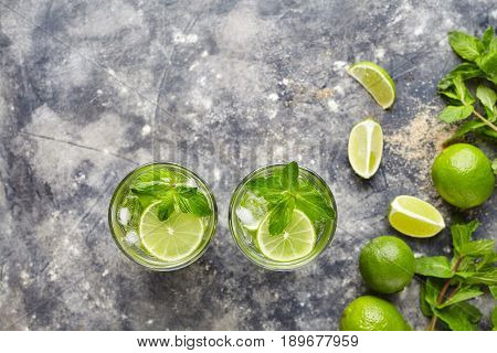 Mojito cocktail traditional alcohol bar drink top view copy space two highball glass, summer tropical vacation beverage with rum, citrus slice, mint, lime juice, soda water and ice on concrete table.