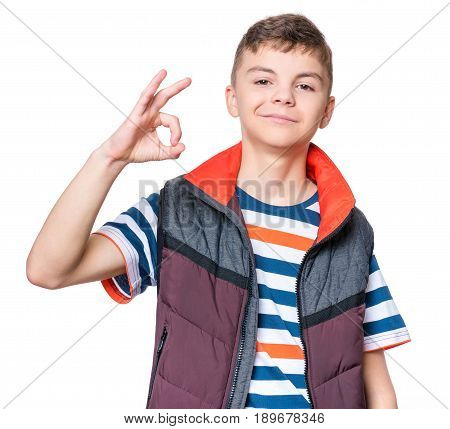 Half-length emotional portrait of caucasian teen boy wearing blue t-shirt. Funny teenager making ok gesture, isolated on white background. Handsome child smiling looking happy.