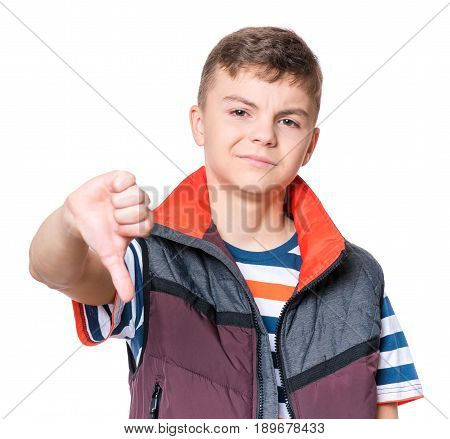 Emotional portrait of unhappy teen boy giving thumbs down hand gesture. Angry child looking with disapproval facial expression, on white background. Negative human face expressions.