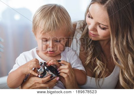 mother and son playing with alarm clock, they sitting indoors on the sofa