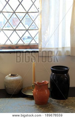 Vertical image of large pottery jugs and tapered candle set at base of curtained window