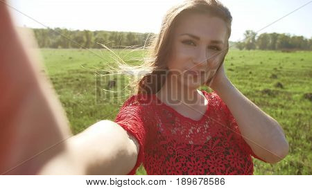 Selfie. girl makes selfie, takes pictures of herself in nature. Girl hair breeze lifestyle