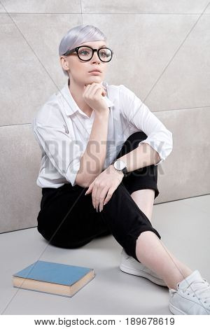 Young woman daydreaming at home, sitting on floor, having book.