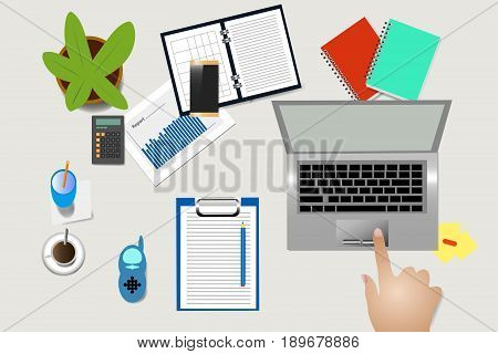 Top view of home office desk with supplies coffee cup and electronic baby monitor. Female hand is touching touchpad of laptop.