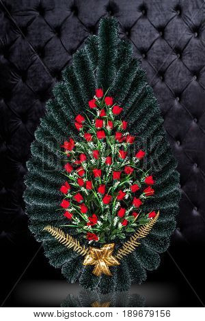Luxury Funeral wreath with red roses isolated on royal dark background. Ritual object for funeral