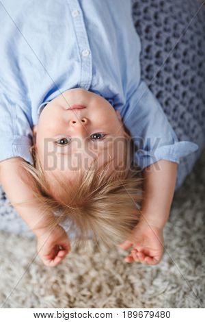 upside down blonde cute boy on pouf