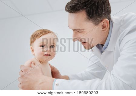 Positive visitor. Caring competent friendly man running a regular checkup on a toddler who sitting on special table and looking excited