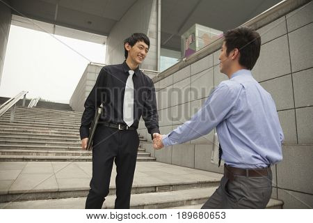 Chinese businessmen shaking hands on city steps