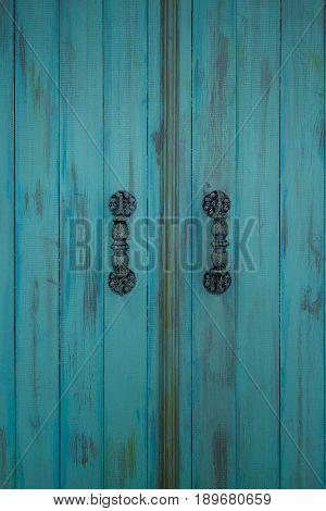 Wooden blue door with metal old door-handle. Retro style.