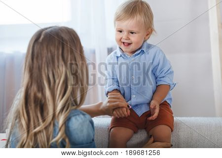 mother and son playing at home, closeup portrait of boy