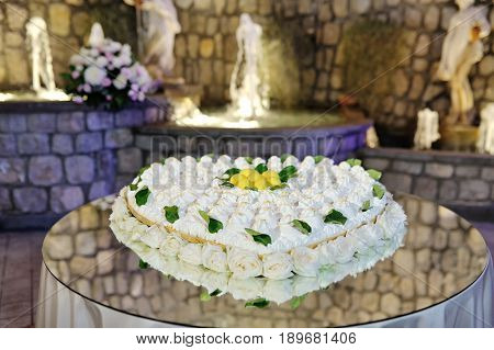Beautiful heart shaped wedding lemon cake decorated with roses on a table