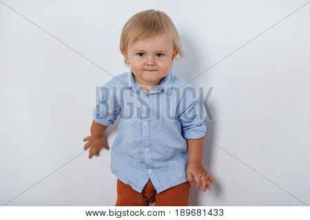 portrait of smiling cute little blonde boy near white wall