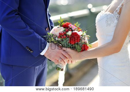 Wedding bouquet bride and groom holding hands on wedding day