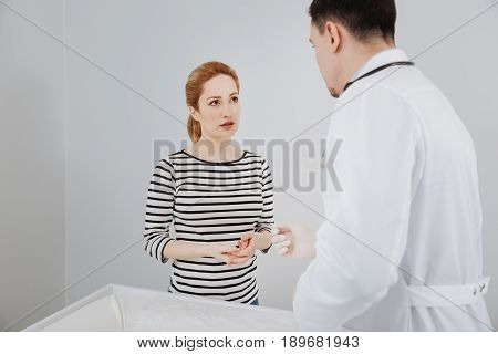 Fruitful conversation. Neat intelligent young lady paying her doctor a visit and asking for his opinion while seeming concerned about her issue