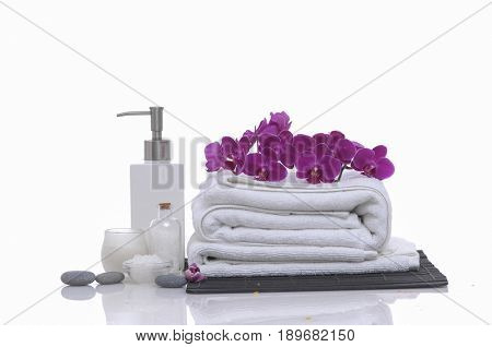 Spa concept with rolled towel, pink orchid,stones, oil