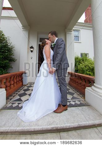 Bride And Groom Kissing On The Steps Of Their Wedding Venue
