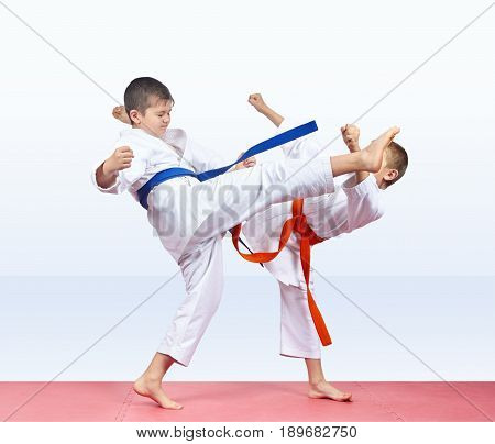 On a red mats children boys are beating kick legs