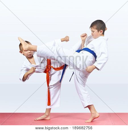 Two karateka beat kicks on the red mats
