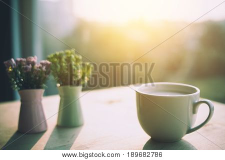 flowers in a vase and cup of coffee on the rustic style background