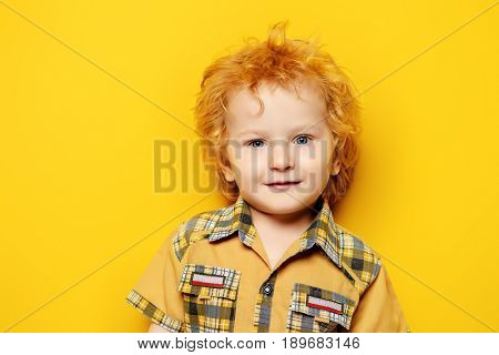 Portrait of a small three year old boy in summer clothes over yellow background. Copy space. Children fashion, summer concept. Happy childhood.