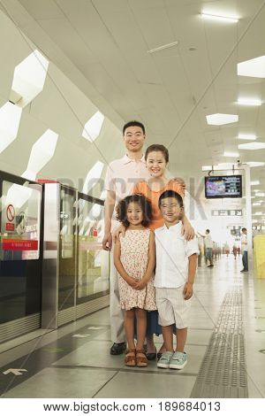 Chinese family standing in subway station