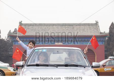 Chinese boy waving Chinese flag out of car window