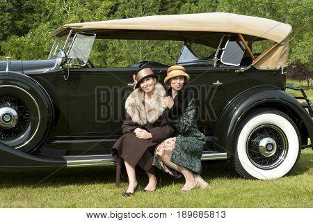 Caucasian women by vintage car