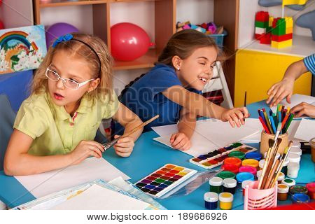 Small students painting in art school class. Child drawing by paints on table. Kid on balloons background. Top view of girl in kindergarten. Drawing education develops creative abilities of children