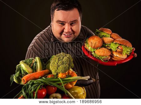 Diet fat man who makes choice between healthy and unhealthy food . Overweight male with hamburgers and vegetables trays trying to lose weight first time on black background.
