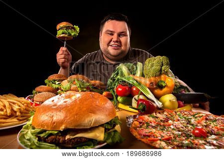 Diet fat man who makes choice between healthy and unhealthy food. Overweight male with hamburgers, french fries and vegetables trays trying to lose weight first time on black background.