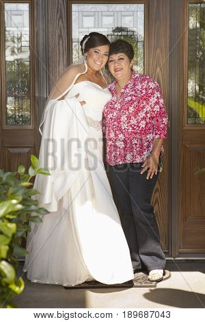 Hispanic bride standing with mother