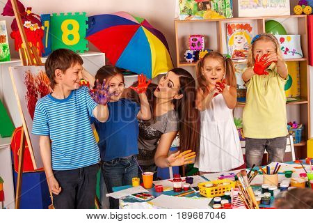 Small students with teacher finger painting in art school class. Teacher cheers children in kindergarten. Craft education develops creative abilities . Kids are fond of painting pictures with palms.