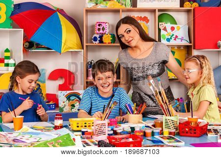 Kids playroom organization of children painting and drawing in kid's club. Craft lesson in primary school. Kindergarten teacher and students work together. Children's club with professional teachers.