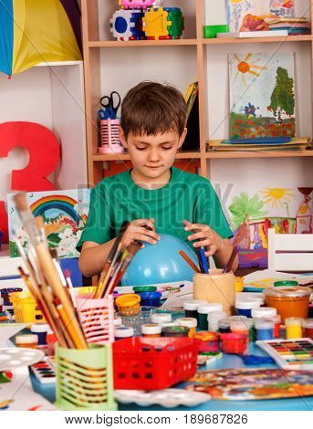 Small student boy painting in art school class. Child drawing by paints on table. Boy in a children's club. Craft drawing education develops creative abilities of children. Boy makes an imaginary