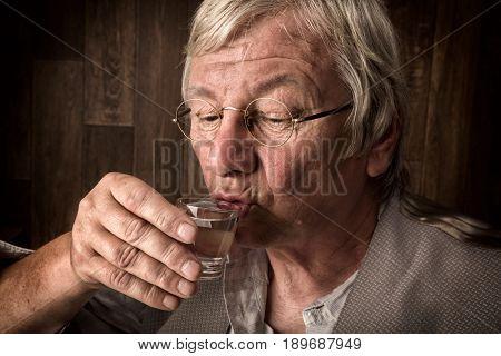 Gray elderly man enjoying a jenever drink in a shot glass