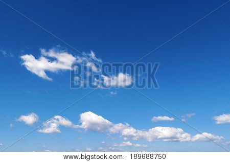 Wispy white clouds float through blue summer sky