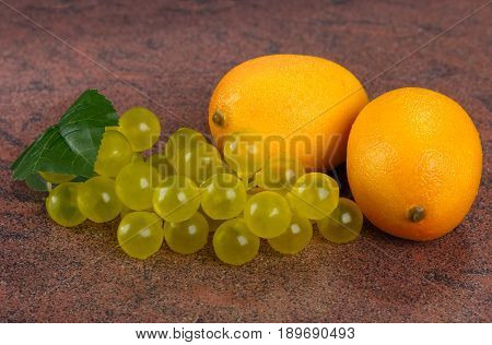 lemons and fake bunch of grapes on granite background