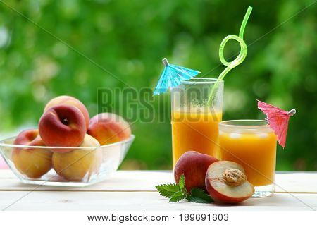 Two glasses of peach juice with umbrellas on a wooden table on a green background. In the background a bowl with peaches.