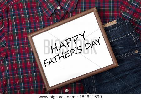 Closeup of whiteboard with a text of happy father's day above a pant and shirt for father concept of father's day