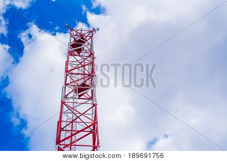 Mobile Phone Communication Antenna Tower With Satellite Dish On Blue Sky Background With Sun Ray Fla