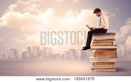 A serious student with laptop tablet in elegant suit sitting on a stack of books in front of cityscape with clouds