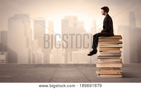 A serious student in elegant suit sitting on a pile of books looking over a brown sepia city landscape