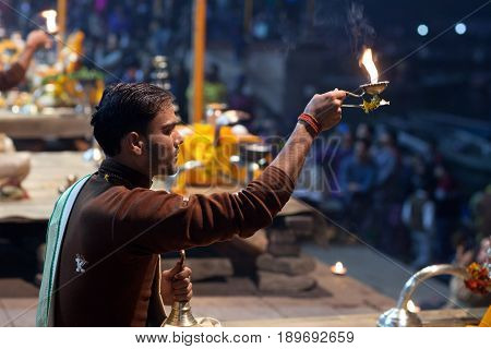 VARANASI, INDIA - JANUARY 3, 2016: Indian Brahmin conducts religious Ganga Maha Aarti ceremony (fire puja) at Dashashwamedh Ghat in Varanasi, Uttar Pradesh, India
