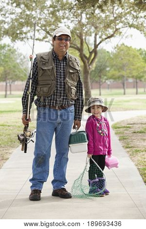 Man carrying fishing equipment with granddaughter