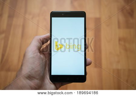 London, United Kingdom, june 5, 2017: Man holding smartphone with Microsoft bing logo on the screen. Laminate wood background.