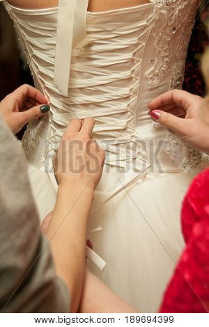 Tying corset on white wedding dress with female hands