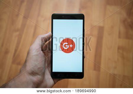 London, United Kingdom, june 5, 2017: Man holding smartphone with Google plus logo on the screen. Laminate wood background.