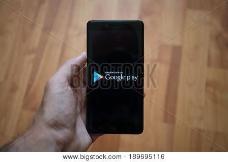 London, United Kingdom, june 5, 2017: Man holding smartphone with Google play logo on the screen. Laminate wood background.