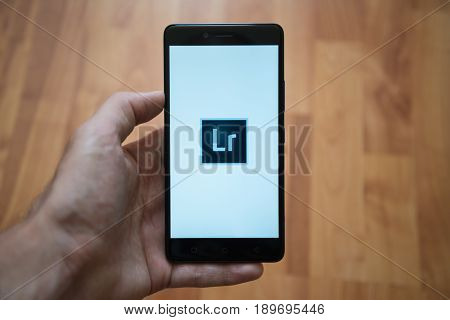 London, United Kingdom, june 5, 2017: Man holding smartphone with Adobe Photoshop Lightroom logo on the screen. Laminate wood background.