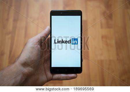 London, United Kingdom, june 5, 2017: Man holding smartphone with Linkedin logo on the screen. Laminate wood background.